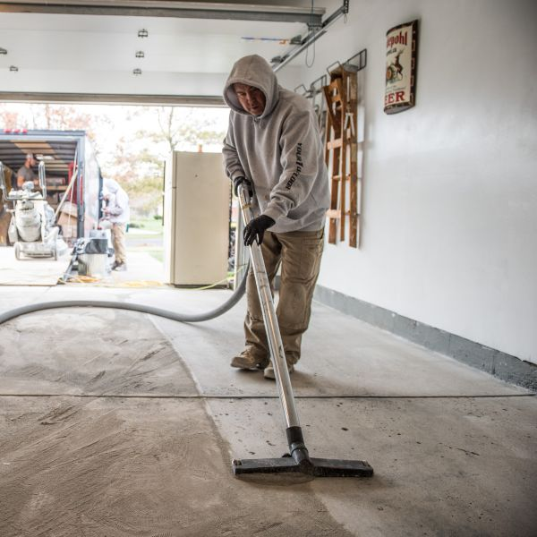 Cleaning up the leftover dust after garage floor grinding.