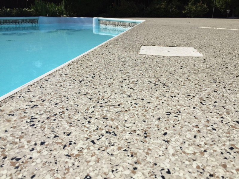 Up close look at pebble beach flake floors on a pool deck.