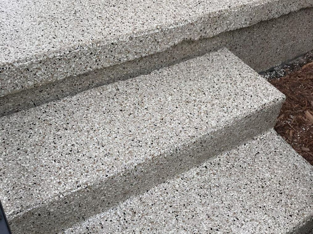 Up close look at flake flooring stairs on a patio.