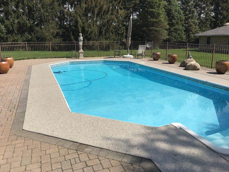 After flake pool deck flooring installed around a pool.
