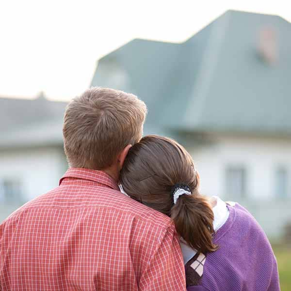 A homeowner couple looking at their beautiful home.